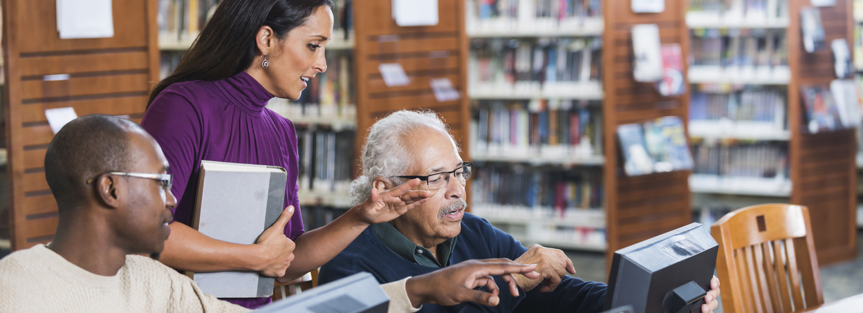 People helping senior man use computer in library – The ...